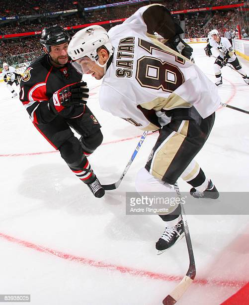 Jason Smith of the Ottawa Senators defends against Miroslav Satan of the Pittsburgh Penguins in the corner at Scotiabank Place on December 6 2008 in...