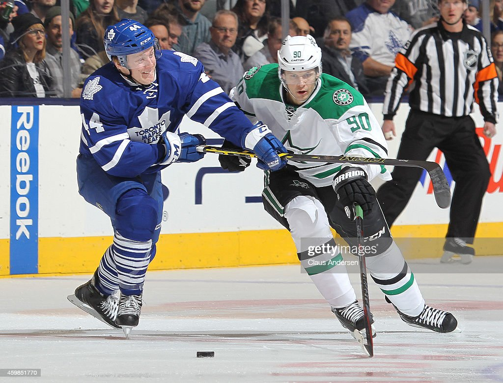 Jason Spezza #90 of the Dallas Stars skates past a checking Morgan Rielly #44 of the Toronto Maple Leafs during an NHL game at the Air Canada Centre on December 2, 2014 in Toronto, Ontario, Canada.