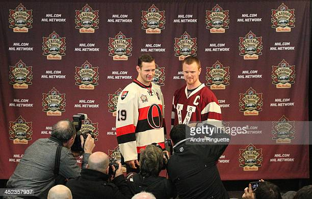 Jason Spezza of the Ottawa Senators and Henrik Sedin of the Vancouver Canucks pose with NHL Heritage Classic jerseys for photographers during the...