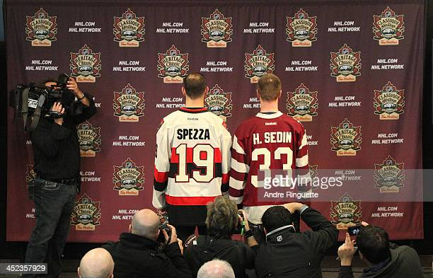 Jason Spezza of the Ottawa Senators and Henrik Sedin the Vancouver Canucks pose with NHL Heritage Classic jerseys for the media during the official...