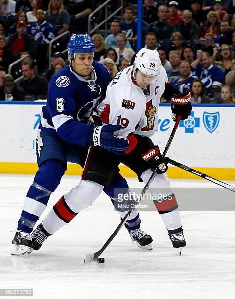 Jason Spezza of the Ottawa Senators is tied up by Sami Salo of the Tampa Bay Lightning at the Tampa Bay Times Forum on March 24 2014 in Tampa Florida