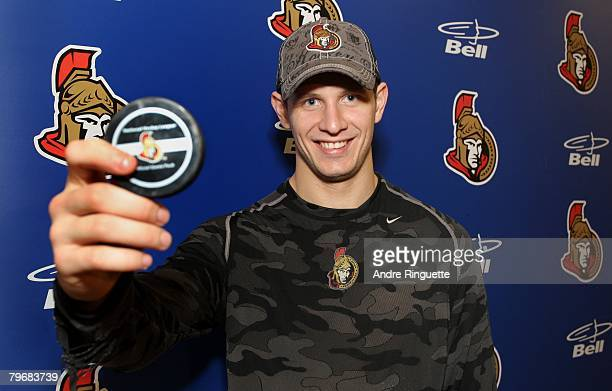 Jason Spezza of the Ottawa Senators poses with the puck he scored his first career hat trick with in a game against the Montreal Canadiens at...