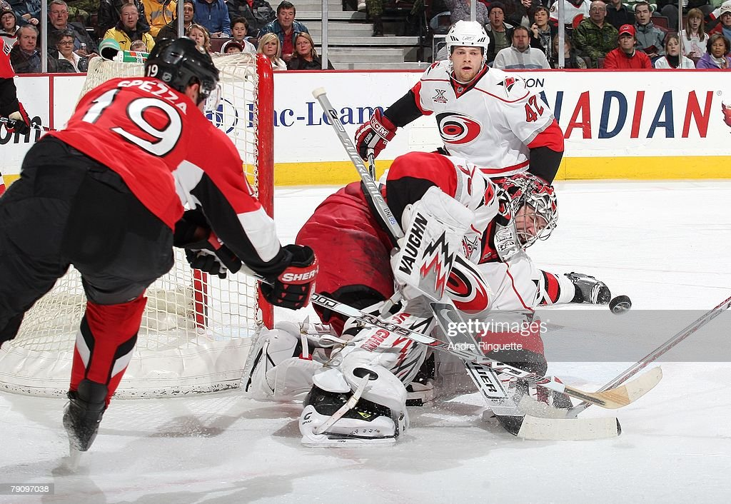 Jason Spezza #19 of the Ottawa Senators reaches to tip a rebound after a save by Cam Ward #30 of the Carolina Hurricanes at Scotiabank Place on January 17, 2008 in Ottawa, Ontario.