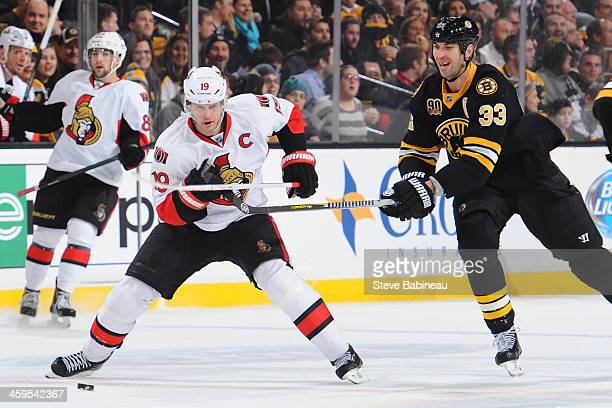 Jason Spezza of the Ottawa Senators skates after the puck against Zdeno Chara of the Boston Bruins at the TD Garden on December 27 2013 in Boston...