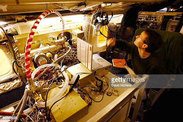 Jason St Clair makes final adjustments to a mass spectrometer for measuring gas phase acids and peroxides aboard a DC8 jet to be used by the National...
