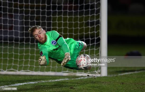 Jason Steele of Brighton and Hove Albion saves a penalty from Mickey Demetriou of Newport County in the shootout during the FA Cup Third Round match...