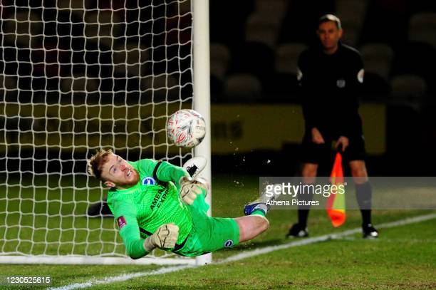 Jason Steele of Brighton & Hove Albion saves a penalty from Scot Bennett of Newport County during the FA Cup Third Round match between Newport County...