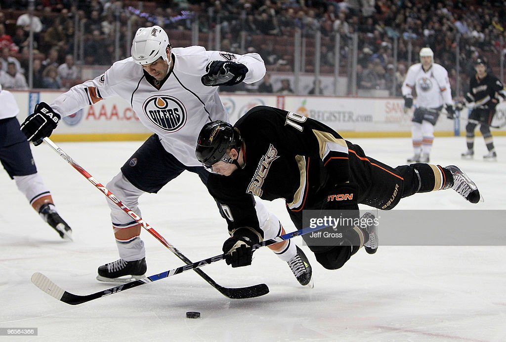 Jason Strudwick #43 of the Edmonton Oilers and Corey Perry #10 of the Anaheim Ducks battle for the puck in the first period at the Honda Center on February 10, 2010 in Anaheim, California.