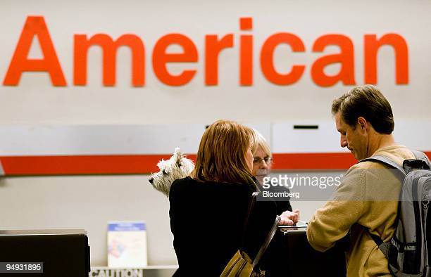 Jason Sweet right and Colleen Blakey left holding their dog Neko check in for a flight with an American Airlines agent at DallasFort Worth...