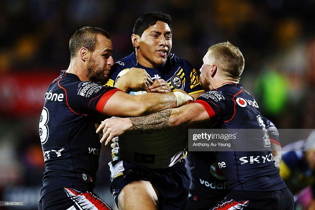 Jason Taumalolo of the Cowboys charges against Simon Mannering and Sam Tomkins of the Warriors during the round 24 NRL match between the New Zealand Warriors and the North Queensland Cowboys at Mt Smart Stadium on August 22, 2015 in Auckland, New Zealand.