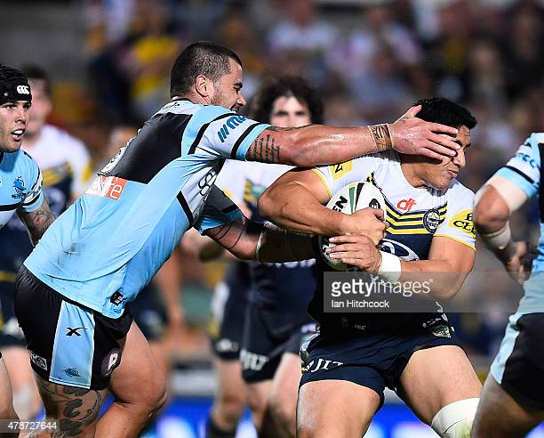 Jason Taumalolo of the Cowboys is tackled by Andrew Fifita of the Sharks during the round 16 NRL match between the North Queensland Cowboys and the...