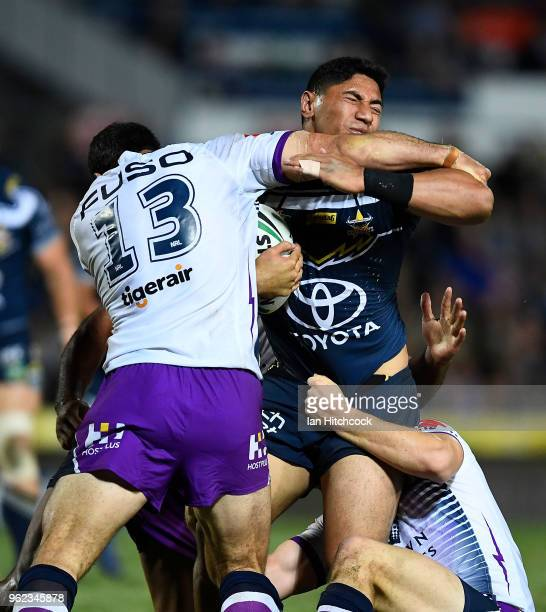 Jason Taumalolo of the Cowboys is tackled by Dale Finucane of the Storm during the round 12 NRL match between the North Queensland Cowboys and the...