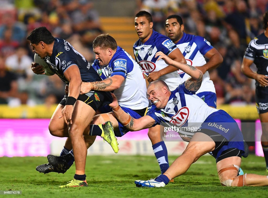 Jason Taumalolo of the Cowboys is tackled by Greg Eastwood and David Klemmer of the Bulldogs during the round six NRL match between the North Queensland Cowboys and the Canterbury Bulldogs at 1300SMILES Stadium on April 14, 2018 in Townsville, Australia.