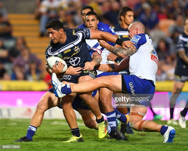Jason Taumalolo of the Cowboys is tackled by Greg Eastwood and David Klemmer of the Bulldogs during the round six NRL match between the North...