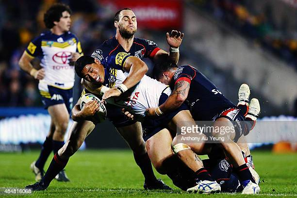 Jason Taumalolo of the Cowboys is tackled by Simon Mannering of the Warriors during the round 24 NRL match between the New Zealand Warriors and the...
