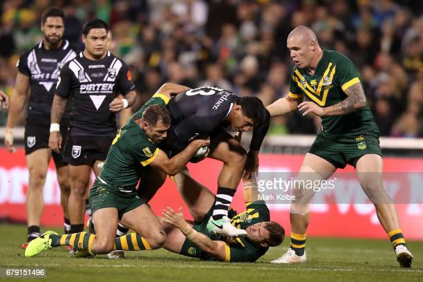 Jason Taumalolo of the Kiwis is tackled by Cameron Smith Trent Merrin and David Klemmer of the Kangaroos during the ANZAC Test match between the...