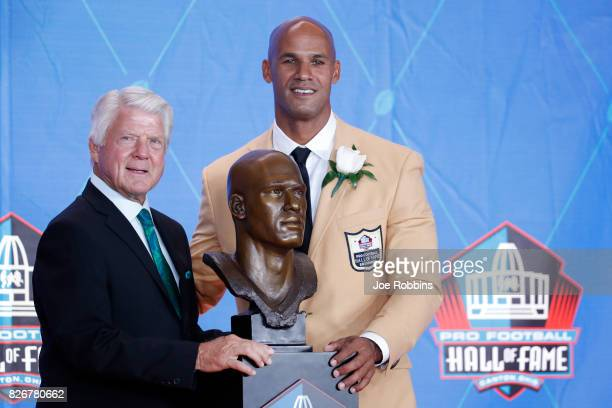 Jason Taylor and presenter Jimmie Johnson pose with Taylor's bust during the Pro Football Hall of Fame Enshrinement Ceremony at Tom Benson Hall of...