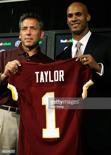 Jason Taylor is presented with a jersey by Redskins head coach Jim Zorn during a news conference at the Redskins Practice Facility July 21 2008 in...