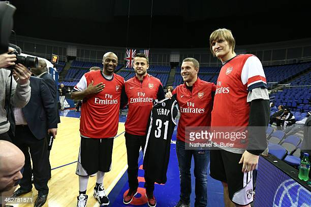 Jason Terry and Andrei Kirilenko of the Brooklyn Nets does a jersey exchange with Lukas Podolski and Lukasz Fabianski of the Arsenal Football Club...