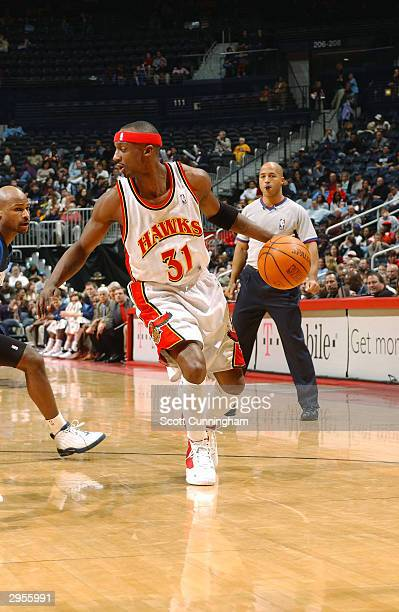 Jason Terry of the Atlanta Hawks drives by Travis Best of the Dallas MavericksFebruary 9 2004 at Philips Arena in Atlanta Georgia NOTE TO USER User...