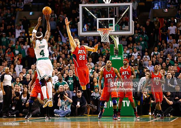 Jason Terry of the Boston Celtics makes a threepoint shot in the final minute of overtime in front of Kyle Korver of the Atlanta Hawks during the...