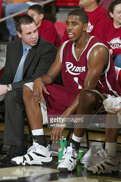 Jason Thompson of the Rider Broncos listens to assistant coach Mike Witcoskie as they sit on the bench against the Cal State Northridge Matadors on...