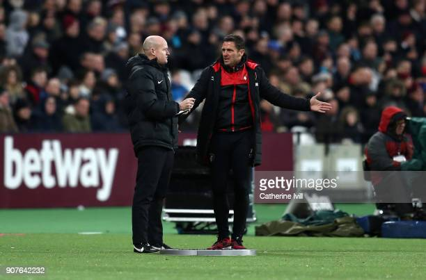 Jason Tindall assistant manager of Bournemouth speaks with fourth official Lee Mason during the Premier League match between West Ham United and AFC...
