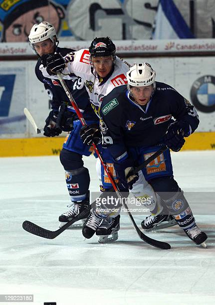 Jason Ulmer of Muenchen and his team mate Klaus Kathan vie for the puck with Lawrence Nycholat of Krefeld during the DEL match between EHC Muenchen...