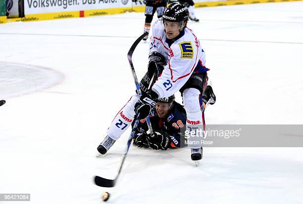Jason Ulmer of Wolfsburg and Matt Hussey of Ingolstadt battle for the puck during the DEL match between Grizzly Adams Wolfsburg and ERC Ingolstadt at...