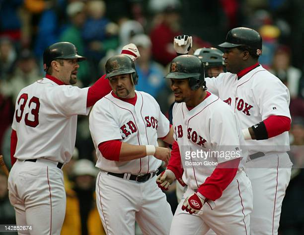 Jason Varitek left congratulates David Ortiz right after Ortiz drove in Kevin Millar second from left and Manny Ramirez third from left while hitting...