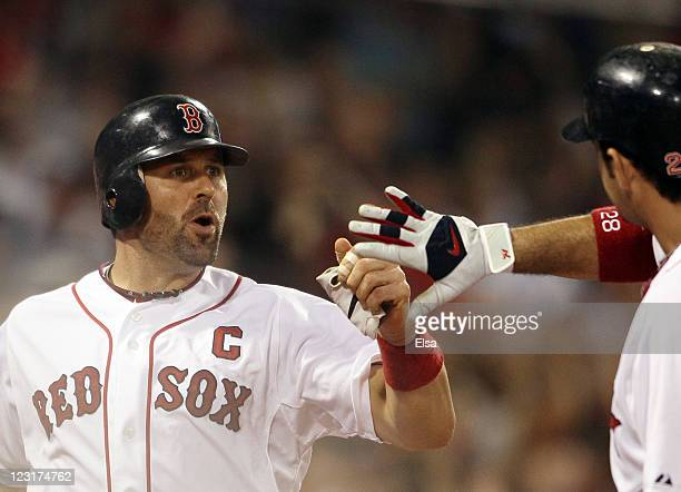 Jason Varitek of the Boston Red Sox is congratulated by Adrian Gonzalez after Varitek scored in the sixth inning against the New York Yankees on...