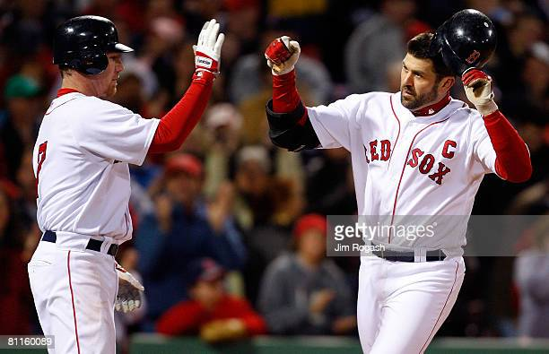 Jason Varitek of the Boston Red Sox is congratulated by teammate J.D. Drew after hitting a home run against the Kansas City Royals at Fenway Park on...