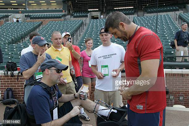Jason Varitek of the Boston Red Sox signs autographs for members of the Wounded Warrior Project before the start of the Red Sox and Baltimore Orioles...