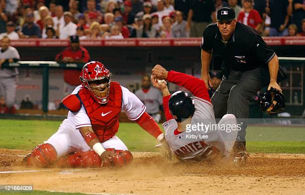 Jason Varitek of the Boston Red Sox slides safety beneath tag of Los Angeles Angels of Anaheim catcher Bengie Molina to score in the fifth inning of...