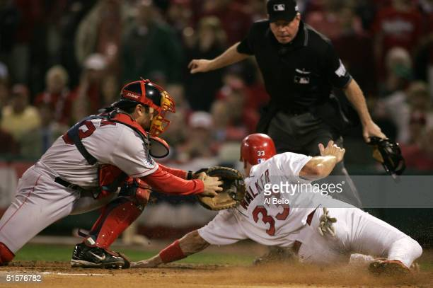 Jason Varitek of the Boston Red Sox tags out Larry Walker of the St Louis Cardinals at the plate during the first inning of game three of the World...