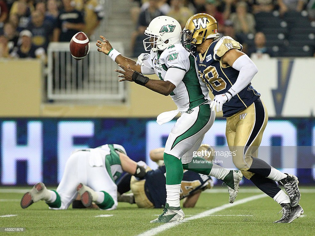 Jason Vega #98 of the Winnipeg Blue Bombers knocks the ball out of the hands of Darian Durant #4 of the Saskatchewan Roughriders in second half action in a CFL game at Investors Group Field on August 7, 2014 in Winnipeg, Manitoba, Canada.