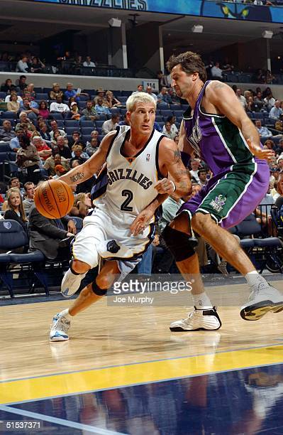 Jason Williams of the Memphis Grizzlies drives baseline against the defense of Toni Kukoc of the Milwaukee Bucks during a game at Fedex Forum on...