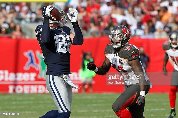 Jason Witten of the Cowboys makes a catch as Danny Lansanah of the Buccaneers closes in to make the tackle during the NFL game between the Dallas...