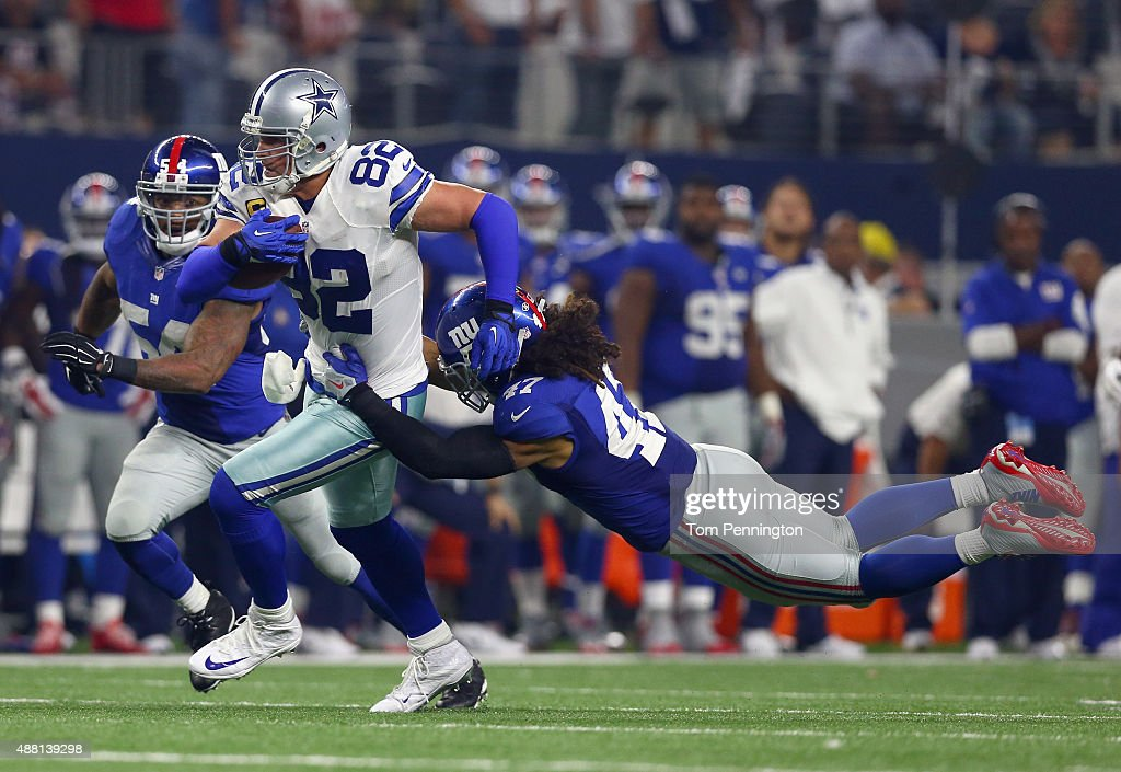 Jason Witten #82 of the Dallas Cowboys carries the ball against Jasper Brinkley #54 of the New York Giants and Uani' Unga #47 of the New York Giants in the fourth quarter at AT&T Stadium on September 13, 2015 in Arlington, Texas.