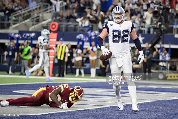 Jason Witten of the Dallas Cowboys in the end zone after catching a touchdown pass against Deshazor Everett of the Washington Redskins at ATT Stadium...