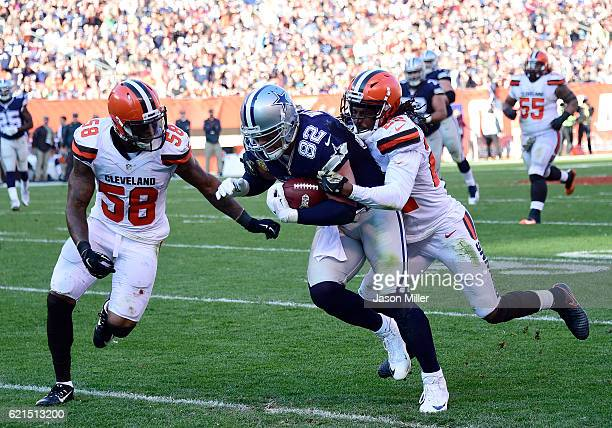 Jason Witten of the Dallas Cowboys runs after the catch against Tramon Williams and Christian Kirksey of the Cleveland Browns at FirstEnergy Stadium...