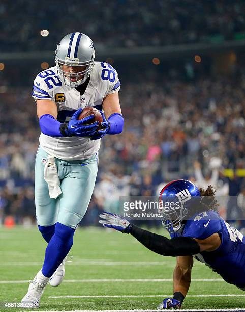 Jason Witten of the Dallas Cowboys takes a touchdown pass into the end zone past Uani' Unga of the New York Giants in the fourth quarter at ATT...
