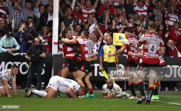 Jason Woodward of Gloucester is mobbed by team mates after scoring the last minute match winning try during the Aviva Premiership match between...