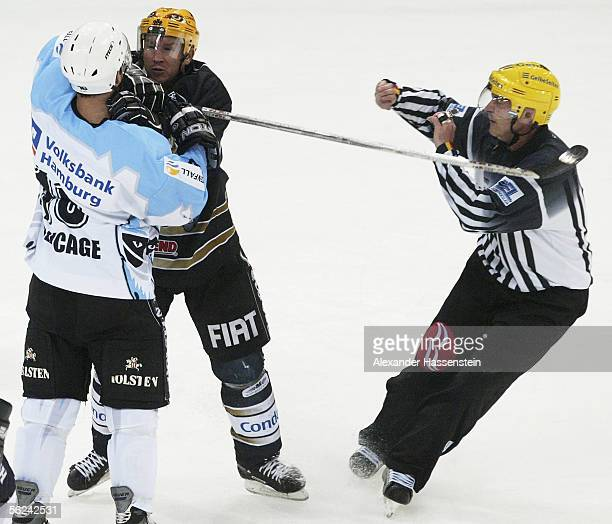 Jason Young of Frankfurt fights with Marc Beaucage of Hamburg whilst referee Gregor Brodnicki looks on during the DEL Bundesliga game between Hamburg...