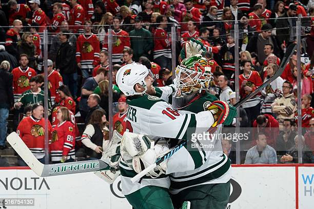 Jason Zucker and goalie Devan Dubnyk of the Minnesota Wild celebrate after defeating the Chicago Blackhawks 3 to 2 in a shoot-out during the NHL game...