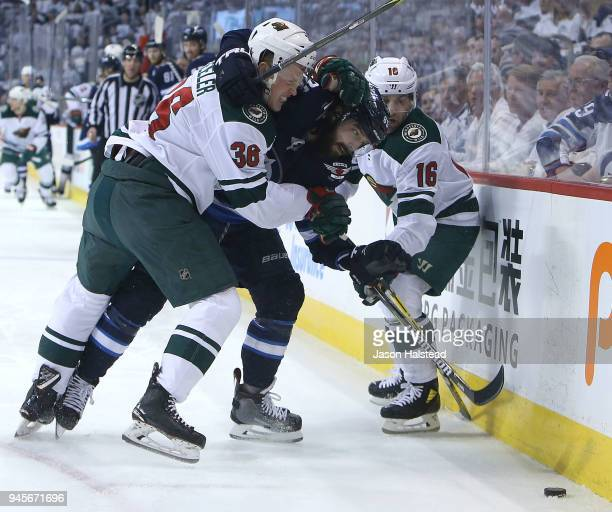 Jason Zucker and Nick Seeler of the Minnesota Wild take on Mathieu Perreault of the Winnipeg Jets in Game One of the Western Conference First Round...