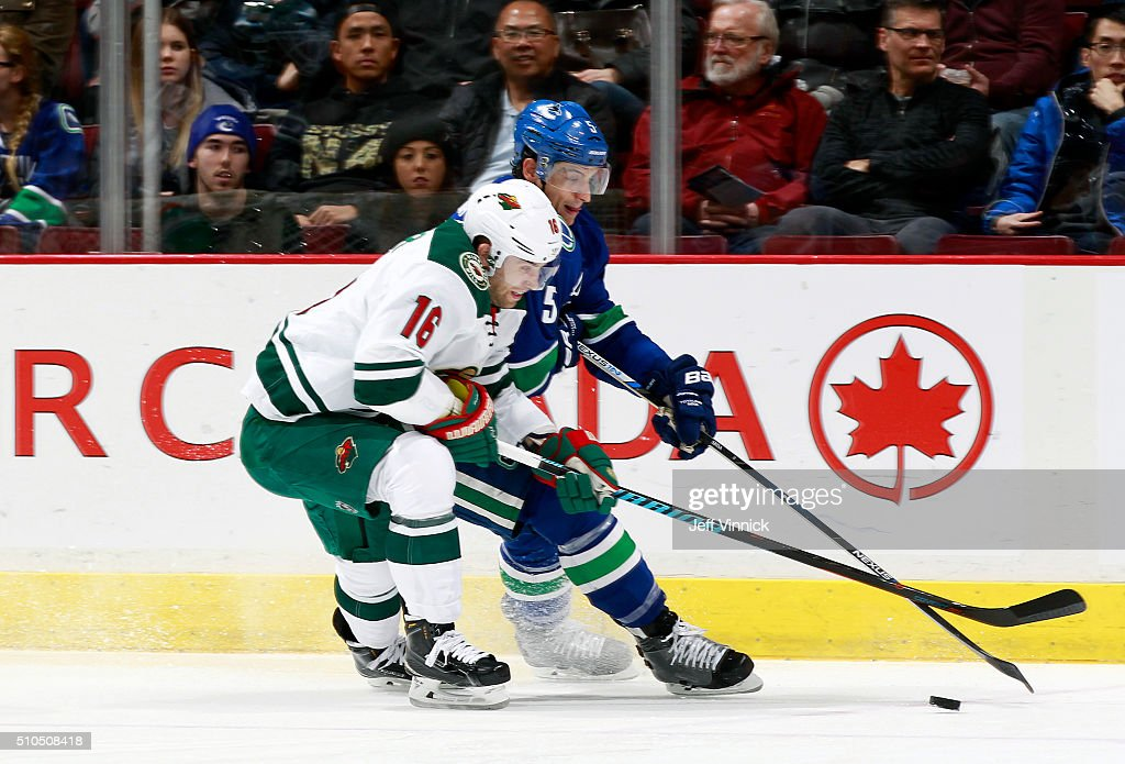 Jason Zucker #16 of the Minnesota Wild and Luca Sbisa #5 of the Vancouver Canucks battle for the puck during their NHL game at Rogers Arena February 15, 2016 in Vancouver, British Columbia, Canada.