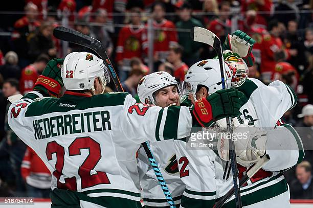 Jason Zucker of the Minnesota Wild celebrates with teammates after defeating the Chicago Blackhawks 3 to 2 in a shoot-out during the NHL game at the...