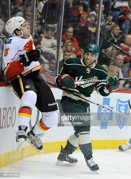 Jason Zucker of the Minnesota Wild checks Brett Carson of the Calgary Flames into the boards during the second period of the game on April 21, 2013...