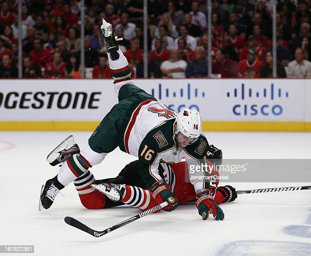Jason Zucker of the Minnesota Wild falls over Johnny Oduya of the Chicago Blackhawks in Game One of the Western Conference Quarterfinals during the...